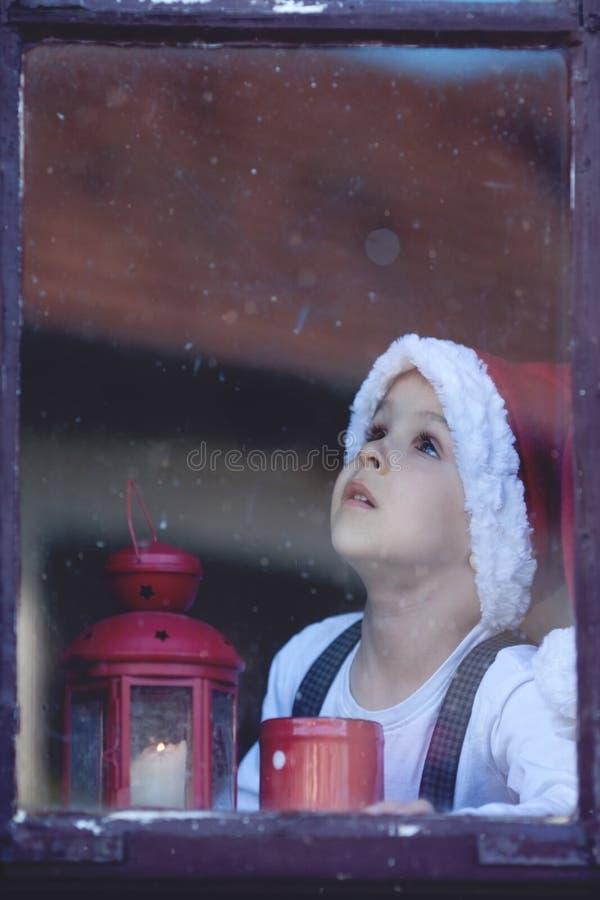 Muchacho adorable, mirando a través de ventana, fotografía de archivo