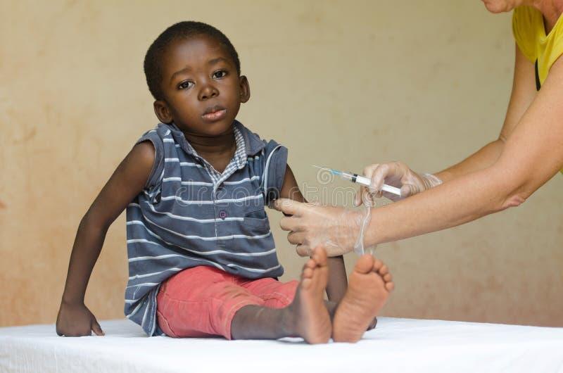 Muchacho africano triste listo para conseguir una inyección de una enfermera voluntaria en Bamako, Malí fotografía de archivo