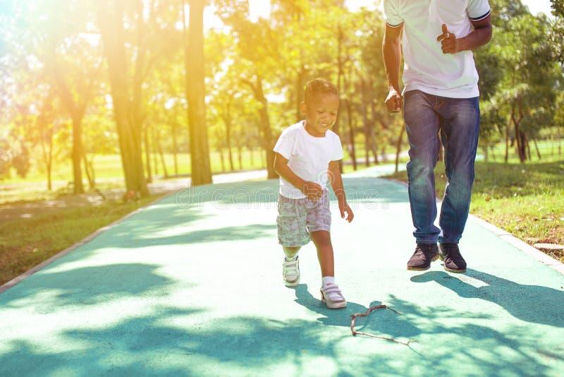 Muchacho afroamericano que camina y que juega con el papá en parque verde fotografía de archivo