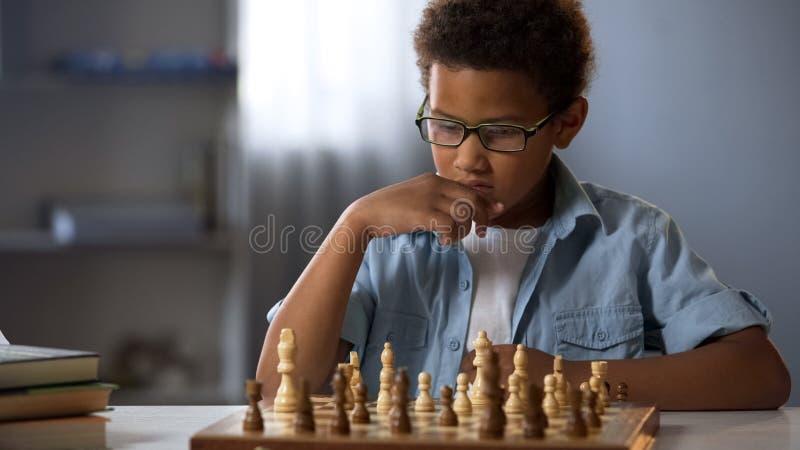 Muchacho afroamericano que piensa lógicamente hacia fuera la estrategia en jugar al ajedrez, afición foto de archivo