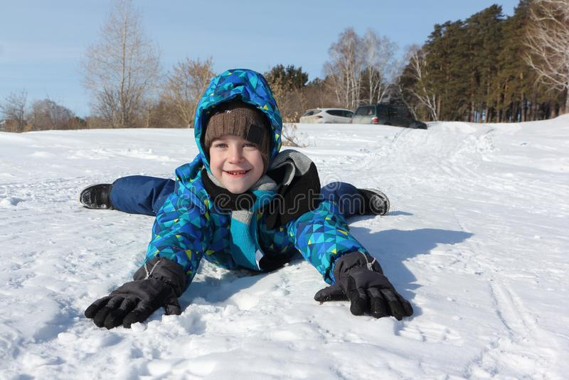 Muchacho alegre feliz que miente en la nieve en invierno fotografía de archivo libre de regalías