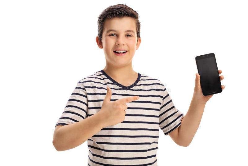 Muchacho alegre que celebra un teléfono y señalar fotografía de archivo libre de regalías