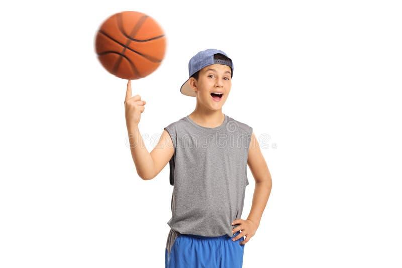 Muchacho alegre que hace girar un baloncesto en su finger fotos de archivo