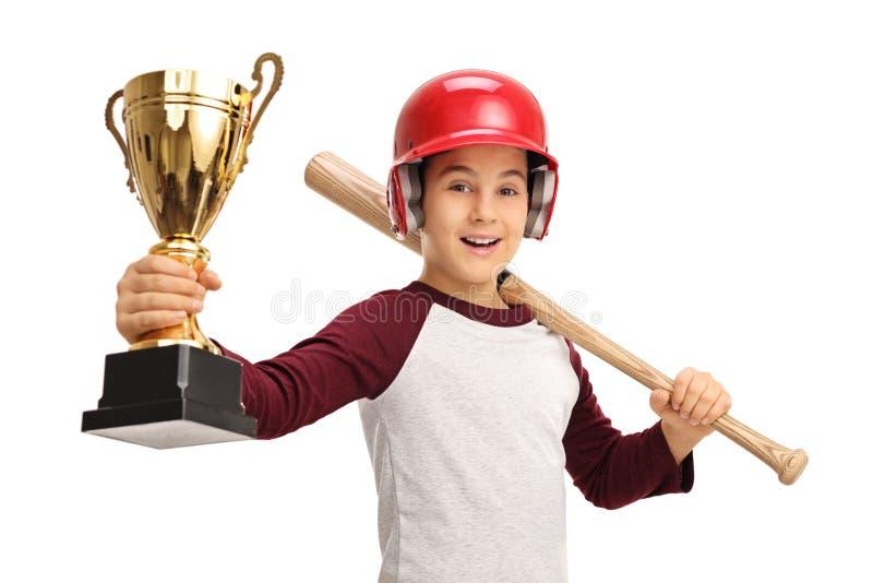 Muchacho alegre que sostiene el trofeo y el bate de béisbol de oro imagen de archivo libre de regalías