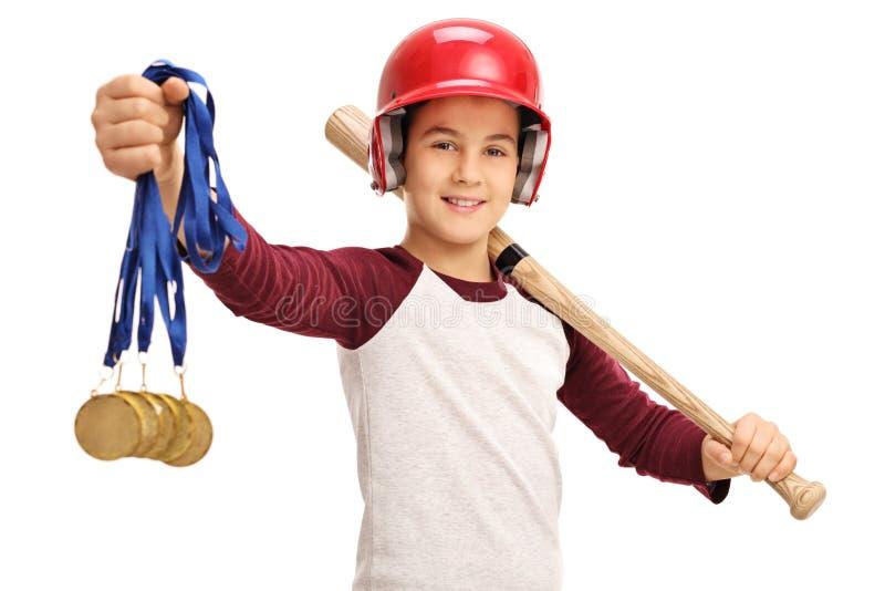 Muchacho alegre que sostiene medallas de oro y un bate de béisbol fotos de archivo libres de regalías
