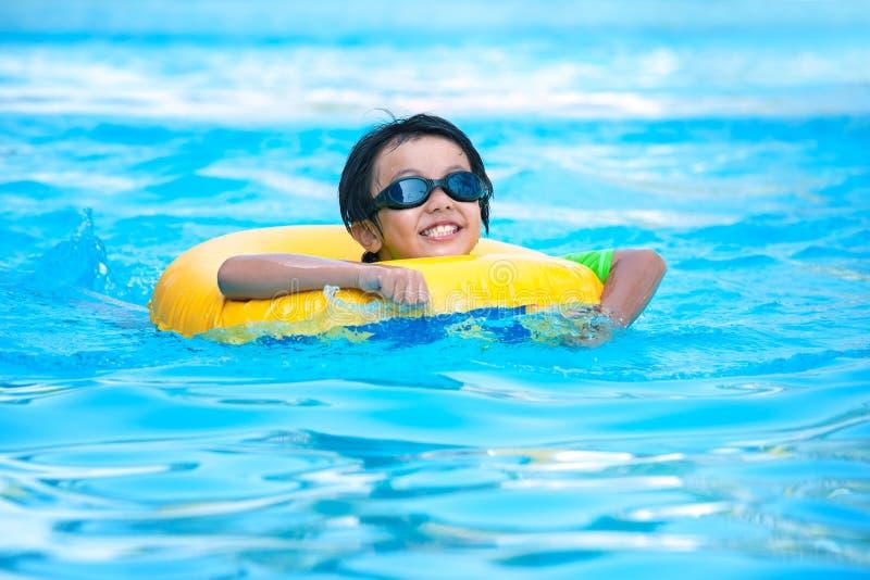 Muchacho asiático en tubo que aprende nadar imagen de archivo libre de regalías