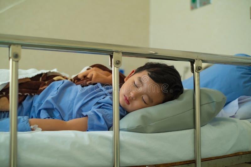 Muchacho asiático enfermo del niño 2 años del enfermo de mentira en cama de hospital fotos de archivo