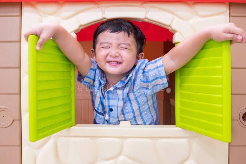 Muchacho asiático feliz del niño que juega con la casa del juguete de la ventana imagenes de archivo