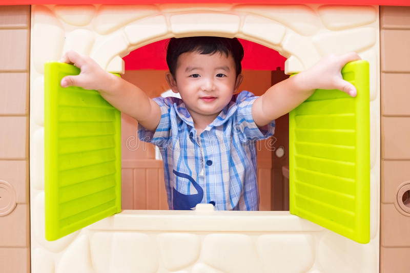 Muchacho asiático feliz del niño que juega la casa del juguete de la ventana en patio imagenes de archivo