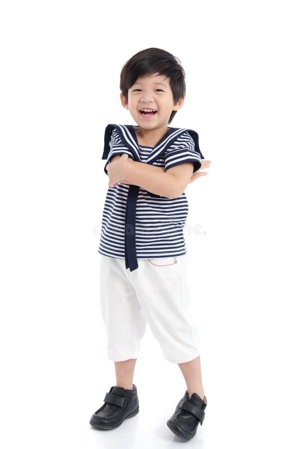 Muchacho asiático feliz que se sienta en el fondo blanco imagen de archivo libre de regalías