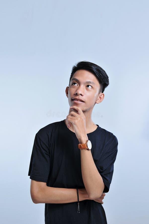 Muchacho asiático joven hermoso que lleva la camiseta y el reloj negros con la mano en la barbilla que piensa en la pregunta, exp fotografía de archivo