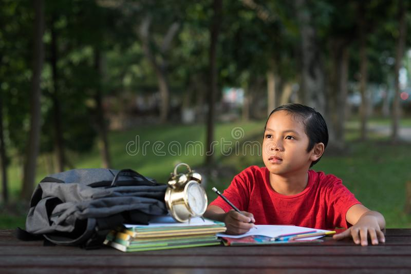 Muchacho asiático joven que estudia en el parque mientras que mira el espacio vacío imagen de archivo