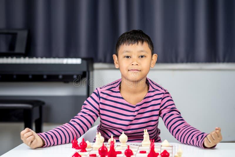 Muchacho asiático joven que juega a ajedrez en el cuarto fotos de archivo libres de regalías