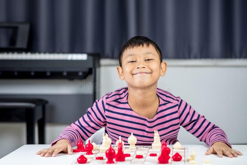 Muchacho asiático joven que juega a ajedrez en el cuarto fotografía de archivo libre de regalías