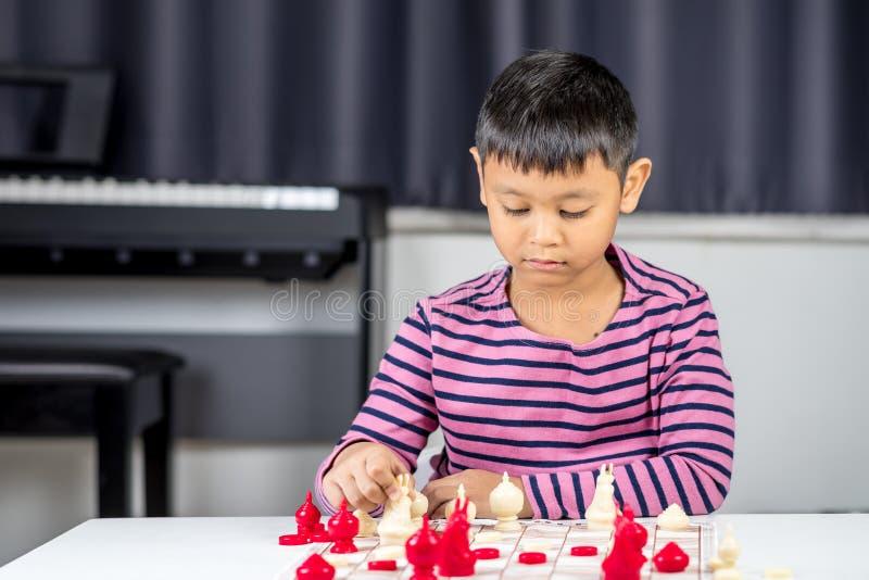 Muchacho asiático joven que juega a ajedrez en el cuarto imagenes de archivo