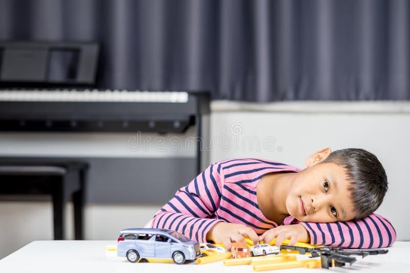 Muchacho asiático joven que juega el juguete del coche en el cuarto imagen de archivo