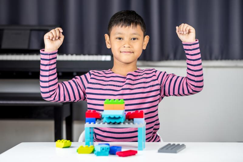 Muchacho asiático joven que juega y que construye con el ladrillo plástico colorido fotos de archivo libres de regalías
