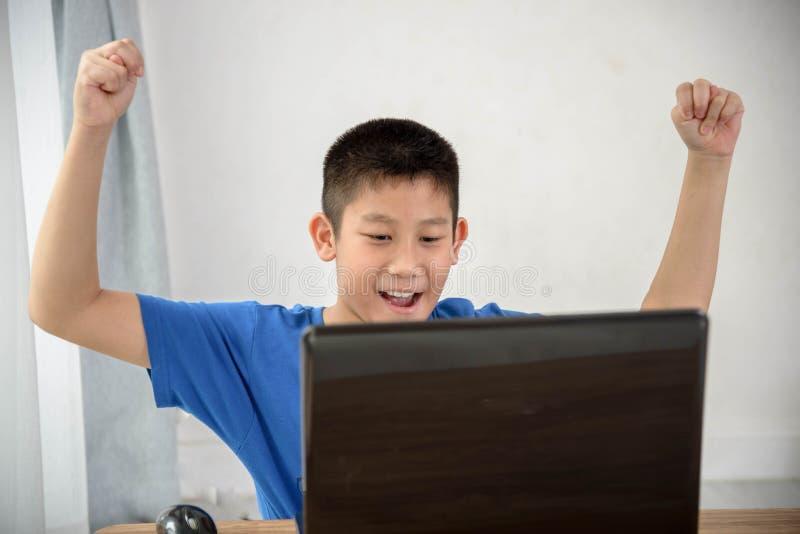 Muchacho asiático joven que usa tecnología del ordenador portátil en casa fotos de archivo