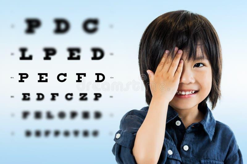 Muchacho asiático lindo que hace la prueba del ojo fotografía de archivo