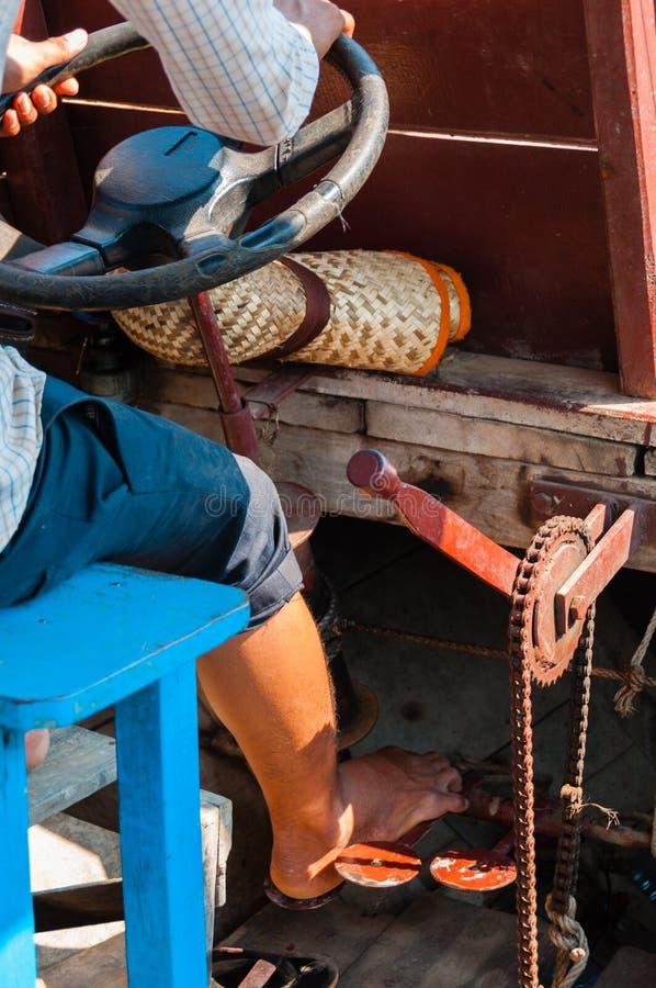 Muchacho asiático que conduce el barco en el río foto de archivo