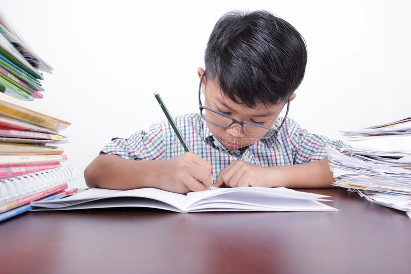 Muchacho asiático que estudia seriamente en un escritorio y un fondo blanco fotos de archivo libres de regalías