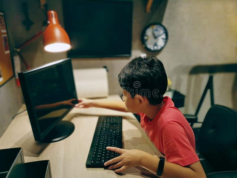 Muchacho asi?tico que lleva la camiseta roja usando el ordenador en el cuarto imagenes de archivo