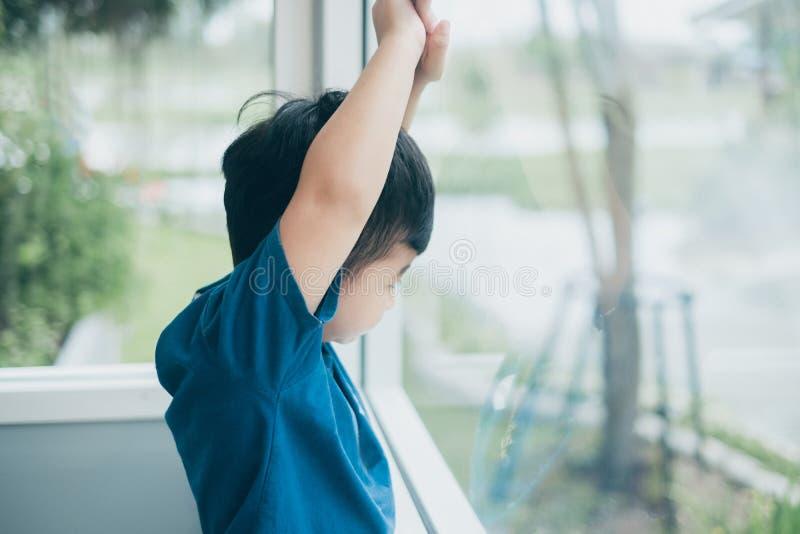 Muchacho asiático que mira fuera de la ventana, esperando alguien fotos de archivo libres de regalías