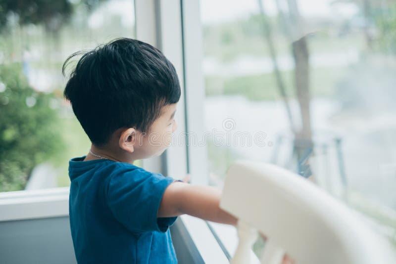 Muchacho asiático que mira fuera de la ventana, esperando alguien imagenes de archivo