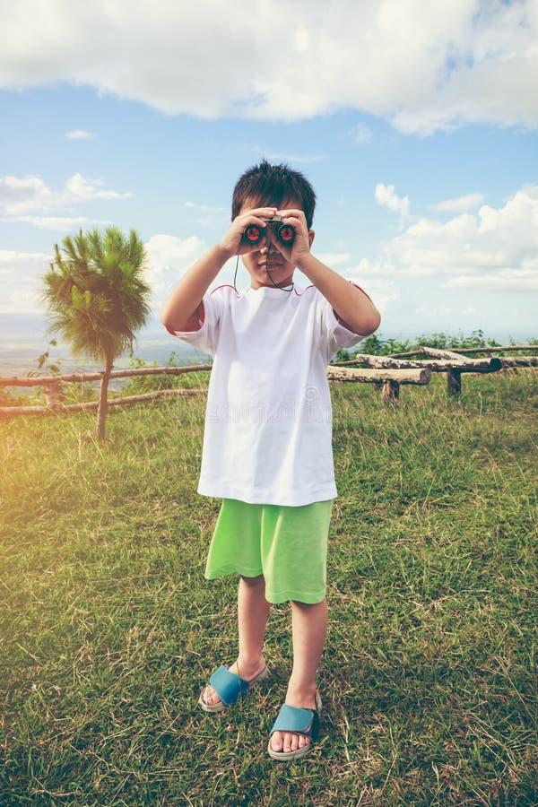 Muchacho asiático que mira a través de un telescopio Día de fiesta relajante del niño V imagenes de archivo