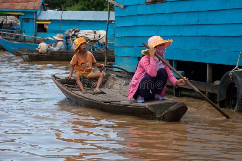 Muchacho asiático que se sienta con la madre en el barco en el río cerca de thei foto de archivo libre de regalías