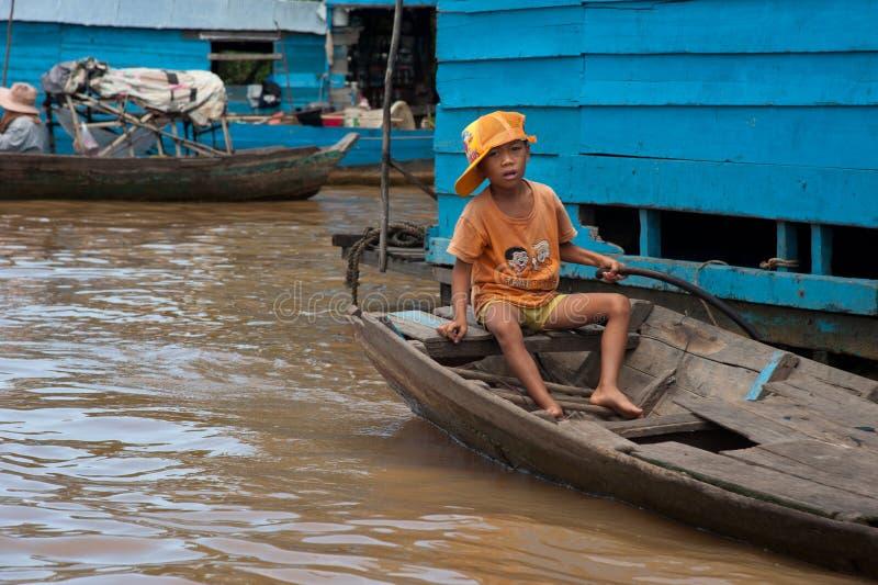 Muchacho asiático que se sienta en el barco en el río cerca de su casa imagen de archivo