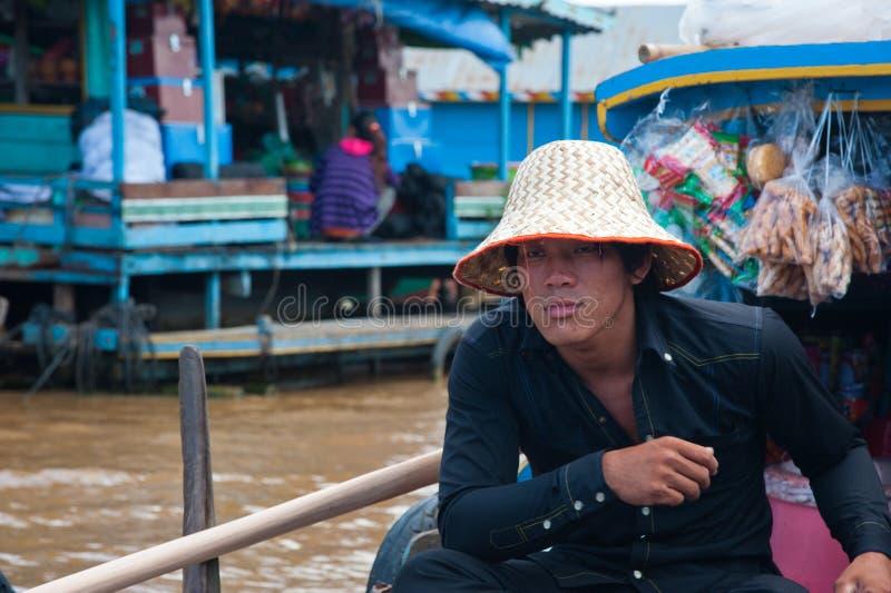 Muchacho asiático que se sienta en el barco y que vende algunos recuerdos fotos de archivo