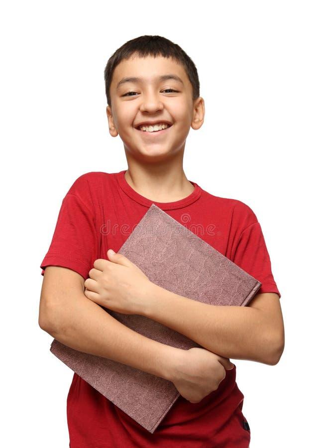 Muchacho asiático sonriente que sostiene el libro grande imagenes de archivo