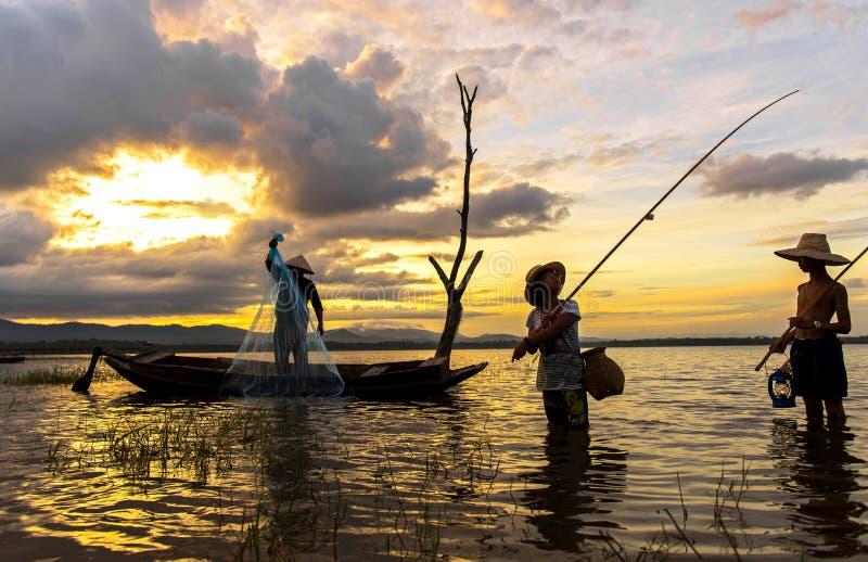 Muchacho asiático y muchacha que juegan en el río con el pescador, fotos de archivo