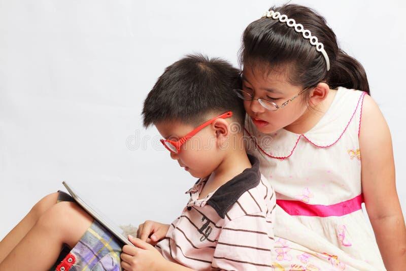 Muchacho asiático y muchacha que juegan la tableta imagen de archivo