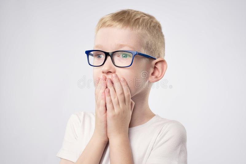 Muchacho asustado del niño con el pelo rubio que lleva a cabo las manos en cara porque él tiene miedo foto de archivo libre de regalías