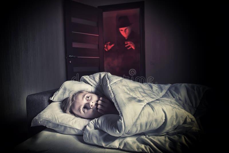 Muchacho asustado que miente en la cama mientras que el extranjero enmascarado fotografía de archivo libre de regalías