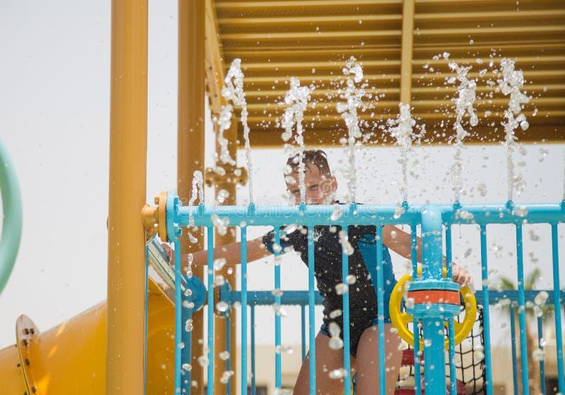 Muchacho blanco joven alegre sonriente feliz que juega feliz en el tobogán acuático imagen de archivo