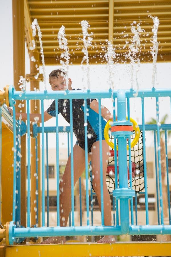 Muchacho blanco joven alegre sonriente feliz que juega feliz en el tobogán acuático fotografía de archivo libre de regalías