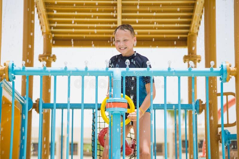 Muchacho blanco joven alegre sonriente feliz que juega feliz en el tobogán acuático fotografía de archivo