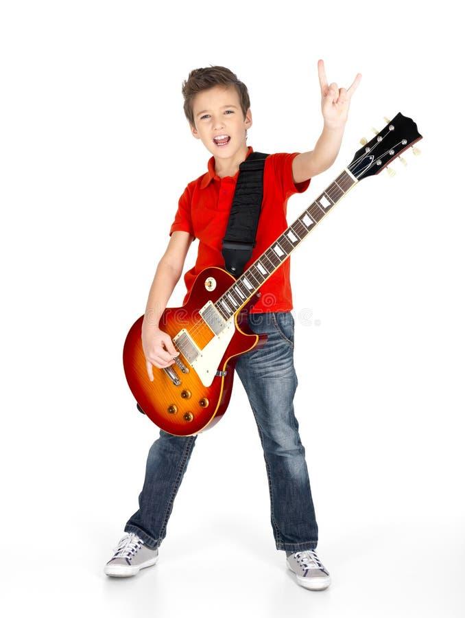 Muchacho blanco joven que sostiene la guitarra eléctrica imagenes de archivo