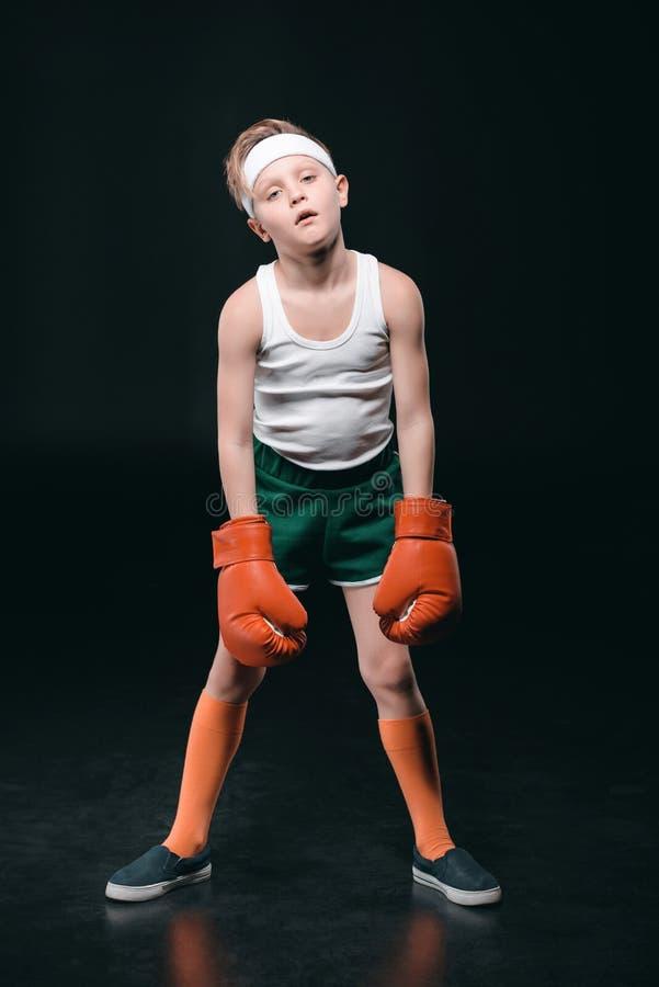 Muchacho cansado en los guantes de boxeo aislados en negro fotos de archivo