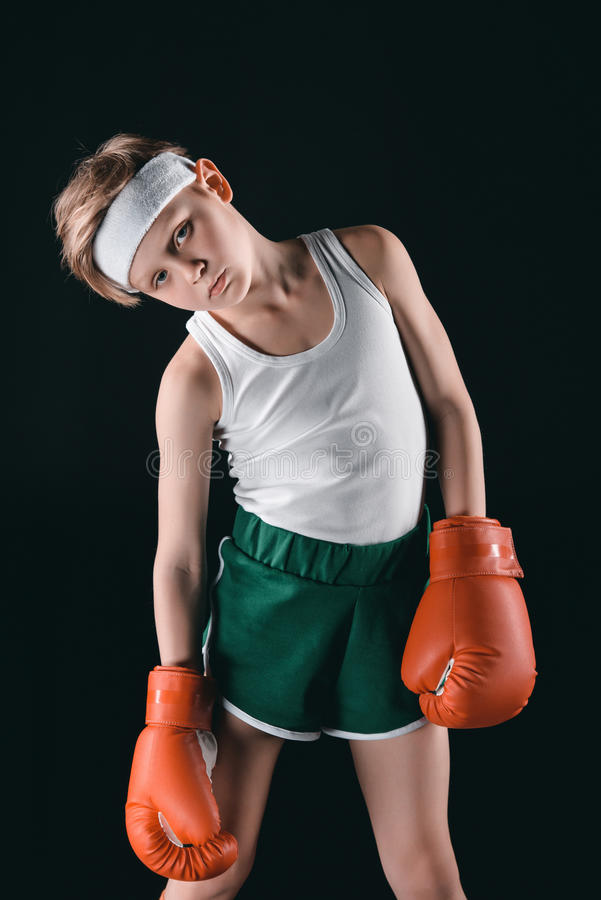 Muchacho cansado en los guantes de boxeo aislados en negro imagen de archivo libre de regalías