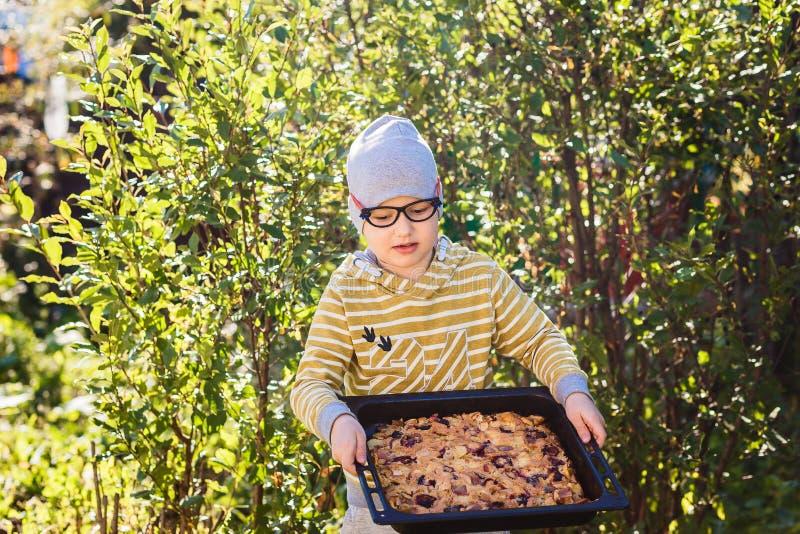 Muchacho caucásico año siete divertidos que sostiene una torta grande de la fruta en el verano imagen de archivo libre de regalías
