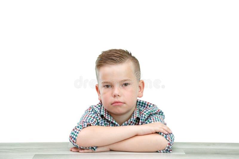 Muchacho caucásico de la escuela-edad en una camisa de tela escocesa en un fondo aislado ligero que se sienta con sus manos dobla fotos de archivo