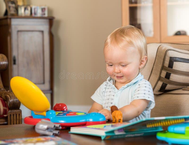 Muchacho caucásico infantil que juega con el ordenador del juguete foto de archivo