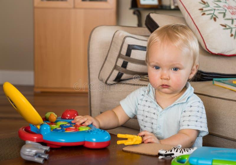 Muchacho caucásico infantil que trabaja en el ordenador del juguete en la tabla imágenes de archivo libres de regalías