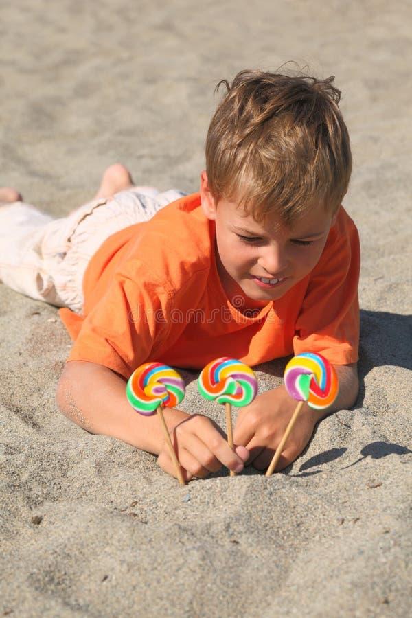 Muchacho caucásico que miente en la playa, lollipops en la arena imagenes de archivo