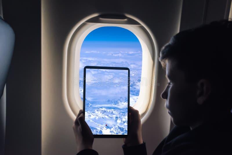 Muchacho caucásico que usa la PC de la tableta que toma la imagen a través de los glaciares de Groenlandia de la ventana del aero foto de archivo libre de regalías