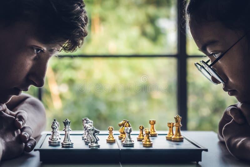 Muchacho caucásico y muchacha asiática que juegan al tablero de ajedrez foto de archivo